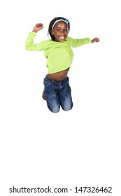Adorable small african child with braids wearing a bright green shirt and blue jeans. The girl is jumping and smiling.