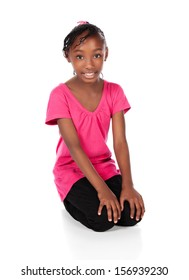 Adorable small african child with braids wearing a bright green shirt and black skinny jeans. The girl is sitting and smiling at the camera.