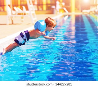 Adorable small boy jumping to the pool, having fun in aquapark, happy summer holidays, day care, active lifestyle, luxury tropical resort