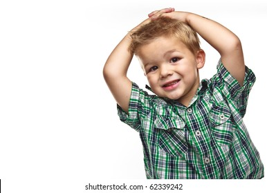 Adorable small boy smiling and wearing plaid with his hands on his head.