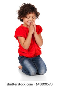 Adorable small caucasian child with curly hair wearing a bright red hooded top and blue jeans. The girl is kneeling and praying.