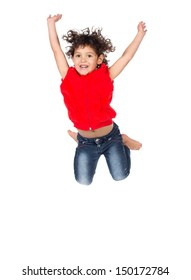 Adorable small caucasian child with curly hair wearing a bright red hooded top and blue jeans. The girl is jumping and smiling.