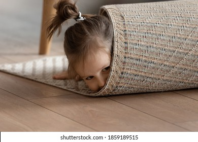 Adorable small girl wrapped in rug lying on warm wooden laminate floor in modern living room alone, close up view. Playtime funny hiding games, professional cleaning carpet company services ad concept