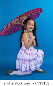 Adorable smiling Asian little girl with long black hair in pig tails and summer dress kneeling while holding pink painted silk umbrella