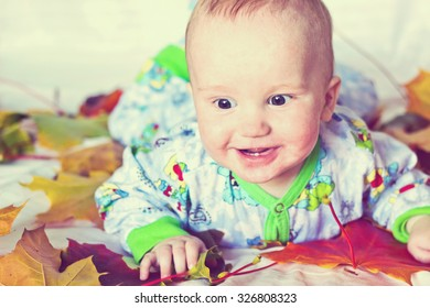 Adorable smiling baby boy with autumn multicolored maple leaves. Studio portrait. Image with vintage filter