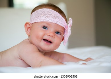 adorable smiling baby girl with pink head bandage