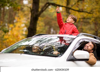 Adorable smiling boy standing in open car sunroof during family trip in autumn forest