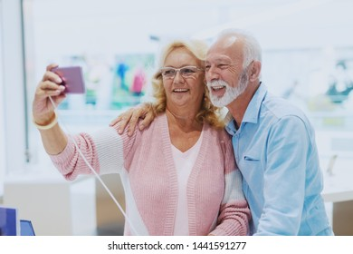 Adorable smiling Caucasian senior couple taking selfie in tech store.