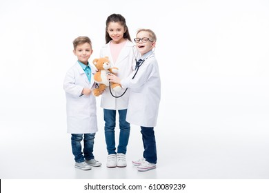 Adorable smiling kids playing doctors with stethoscope, reflex hammer and teddy bear  isolated on white