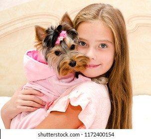 Adorable smiling little girl child holding and playing with puppy yorkshire terrier