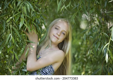 Adorable smiling little girl with long hair posed on the grass