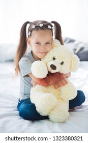 Adorable smiling little girl sitting on a bed hugging a white teddy bear