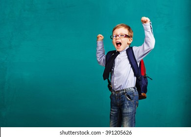 Adorable smiling little kid with big backpack jumping and having fun against blue wall. Looking at camera. School concept. Back to School