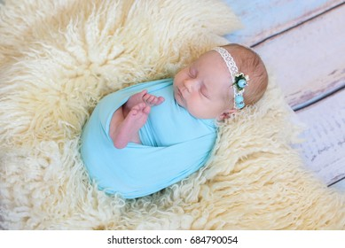 Adorable Smiling newborn baby girl sleeping on milk color blanket in a blue wrap