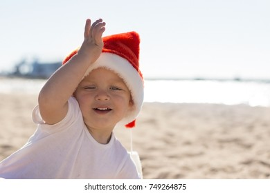 Adorable smiling toddler ina Christmas red hat playing on the beach.