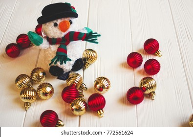 Adorable Snowman toy near Christmas ornaments, children Christmas present, snowman toy with scarf and hat near tree decorations on white wooden board closeup, happy holidays concept