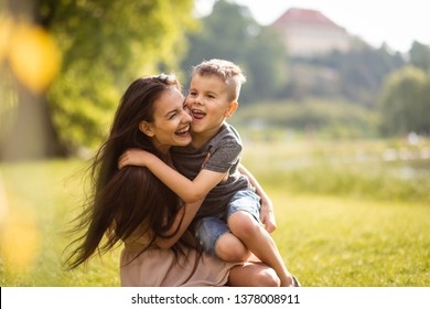 Adorable son sitting on his mother's lap in park