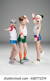 Adorable sporty kids in sportswear standing together and posing isolated on grey, children sport concept