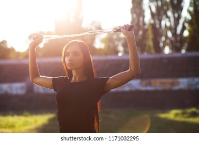 Adorable sporty model stretching before workout at the stadium. Outdoor shot with sun rays. Empty space