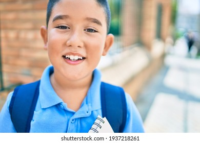 Adorable student boy smiling happy holding book at street of city.
