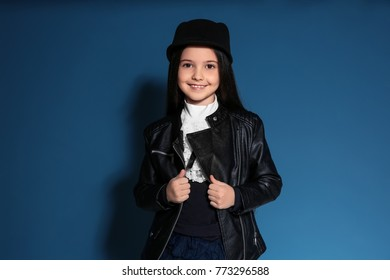 Adorable stylish girl in jacket on color background