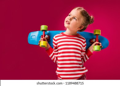 adorable stylish kid posing with penny board isolated on red