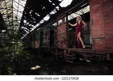 Adorable supermodel posing in the train wagon in the abandoned Red Star graveyard