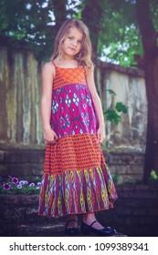 Adorable sweet girl posing for the camera in elegant dress