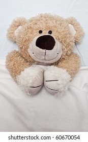 An adorable teddy bear laying in bed, under the sheets.