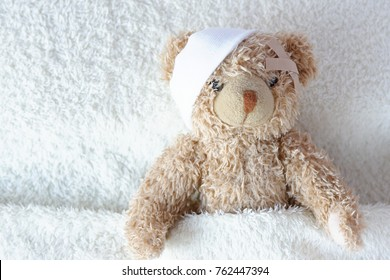 An adorable teddy bear laying in bed, with bandage and plaster, under the sheets.