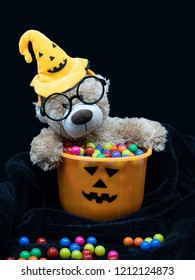 Adorable teddy bear wearing round glasses wearing Halloween hat sit inside orange pumpkin bucket full of candies, put on soft black blanket. Isolated against dark background with copy space to use.