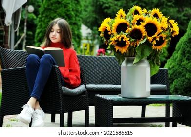 Adorable adolescente en chandail rouge lisant dans le jardin avec grand bouquet de tournesols