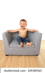 Adorable ten month old baby boy on a sofa chair.