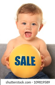 Adorable ten month old baby boy holding a yellow ball with a sale sign. Also available without text, add your own.
