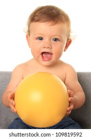 Adorable ten month old baby boy holding a yellow ball. Add your own text onto the ball.