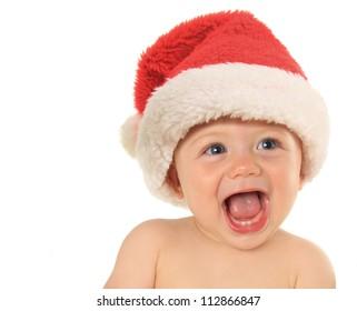 Adorable ten month old baby boy wearing a Santa hat.