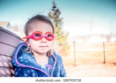 Adorable three-year-old girl, with blond hair, wearing red orange swim goggles and a blue fleece jacket on a beautiful spring day, leans against the side of a brown slide at the playground.