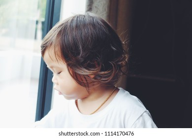 Adorable toddler asian girl with brown hair just woke up and look outside the windows.