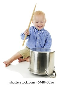 An adorable toddler boy delightedly banging away on a large crock pot with a wooden drumstick.  On a white background.