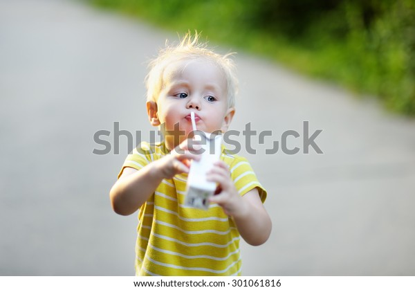 Adorable toddler boy drinking milk or juice outdoors