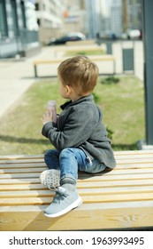Adorable toddler boy in grey sweater has a healthy snack with yogurt on big city street