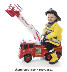 An adorable toddler boy happily riding a toy firetruck in his fireman's outfit.  On a white background.