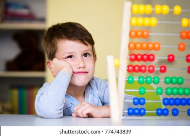 Adorable Toddler boy looking tired and bored while playing with abacus at kindergarten. Child at prechool having tedious expression.