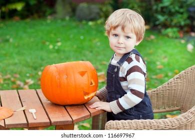 Adorable toddler boy making jack-o-lantern for halloween in autumn garden