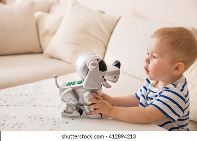 Adorable toddler boy playing with interactive toy. Child with robot dog. indoors. Activities for small children. Communication and digital concept.