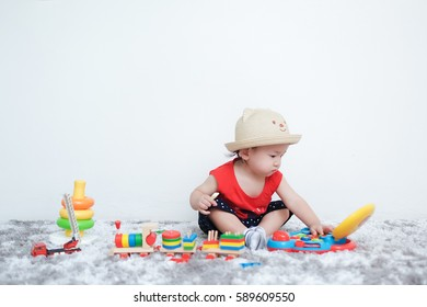 Adorable toddler boy sitting on the carpet and playing colorful toy on a floor