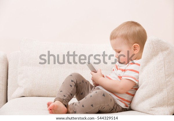 Schattige peuterjongen zittend op de bank in de woonkamer en spelen met smartphone. Kind leert hoe smartphone te gebruiken. Boy sms'en aan de telefoon. - technologie en lifestyle concept