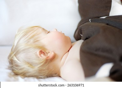 Adorable toddler boy sleeping in a bed