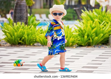 Adorable toddler boy in summer holiday resort in Mauritius, casually dressed, had and sunglasses