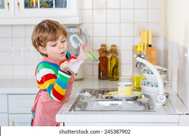 Adorable toddler child washing dishes in domestic kitchen. Little boy having fun with helping his parents with housework. Indoors, kid in colorful clothes.
